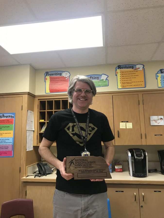 Debate Coach Segrist holds his trophy that he won at Millard North High School.