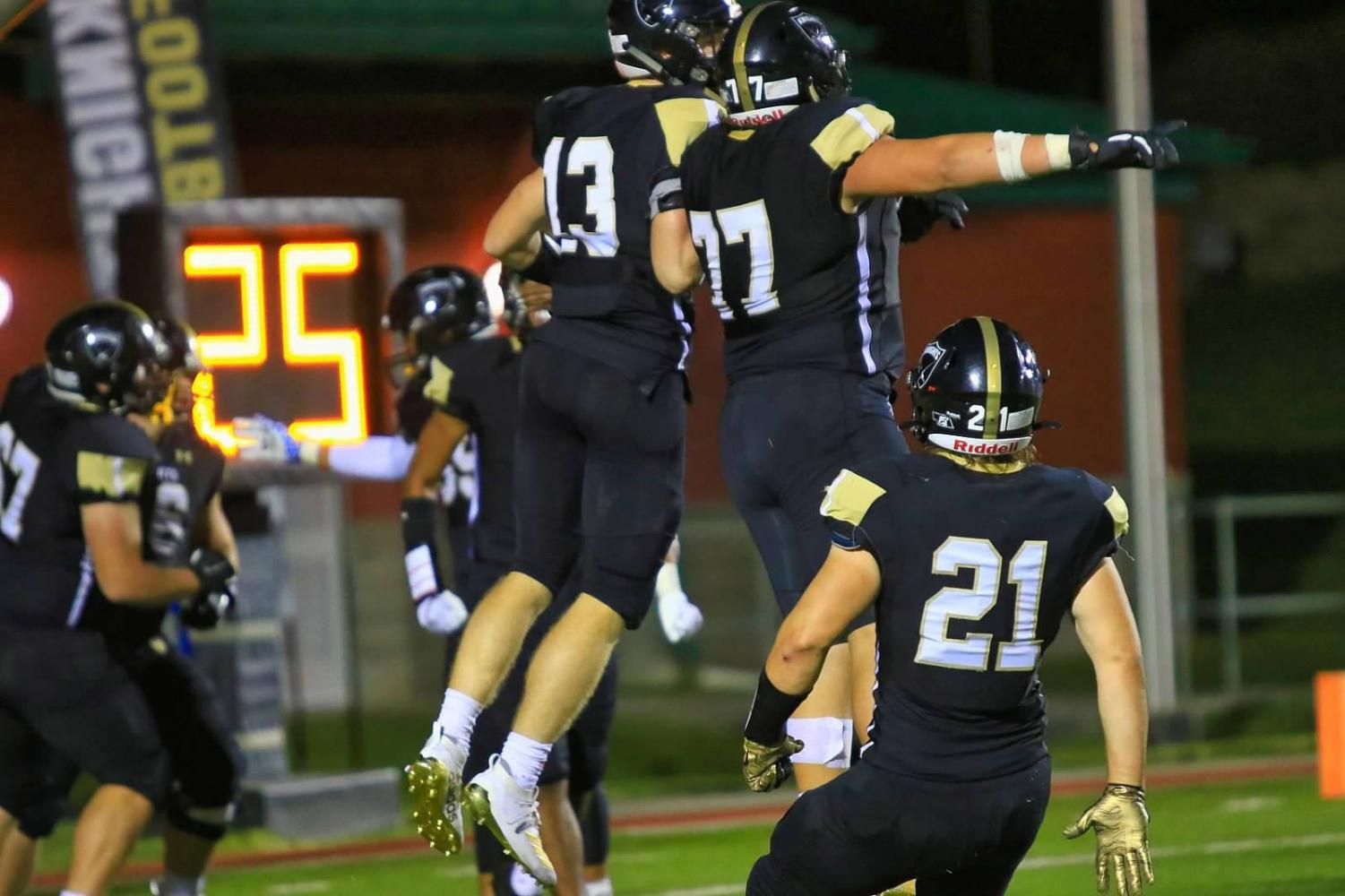 Isaac Gifford (13) celebrates with teammates Xavier Trevino (77) and Nick Halleen (21) after a touchdown.