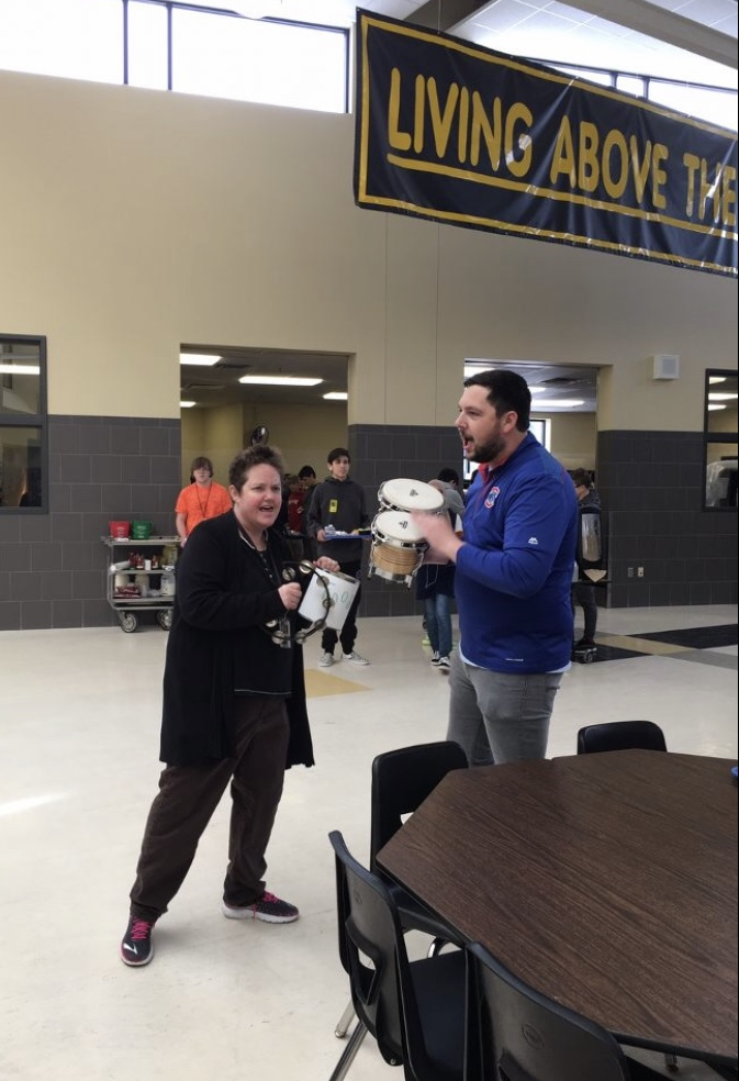 English teacher Julie Krueger and Music teacher Sam Rickert raise awareness for the Food Drive through a musical performance at all three lunches.