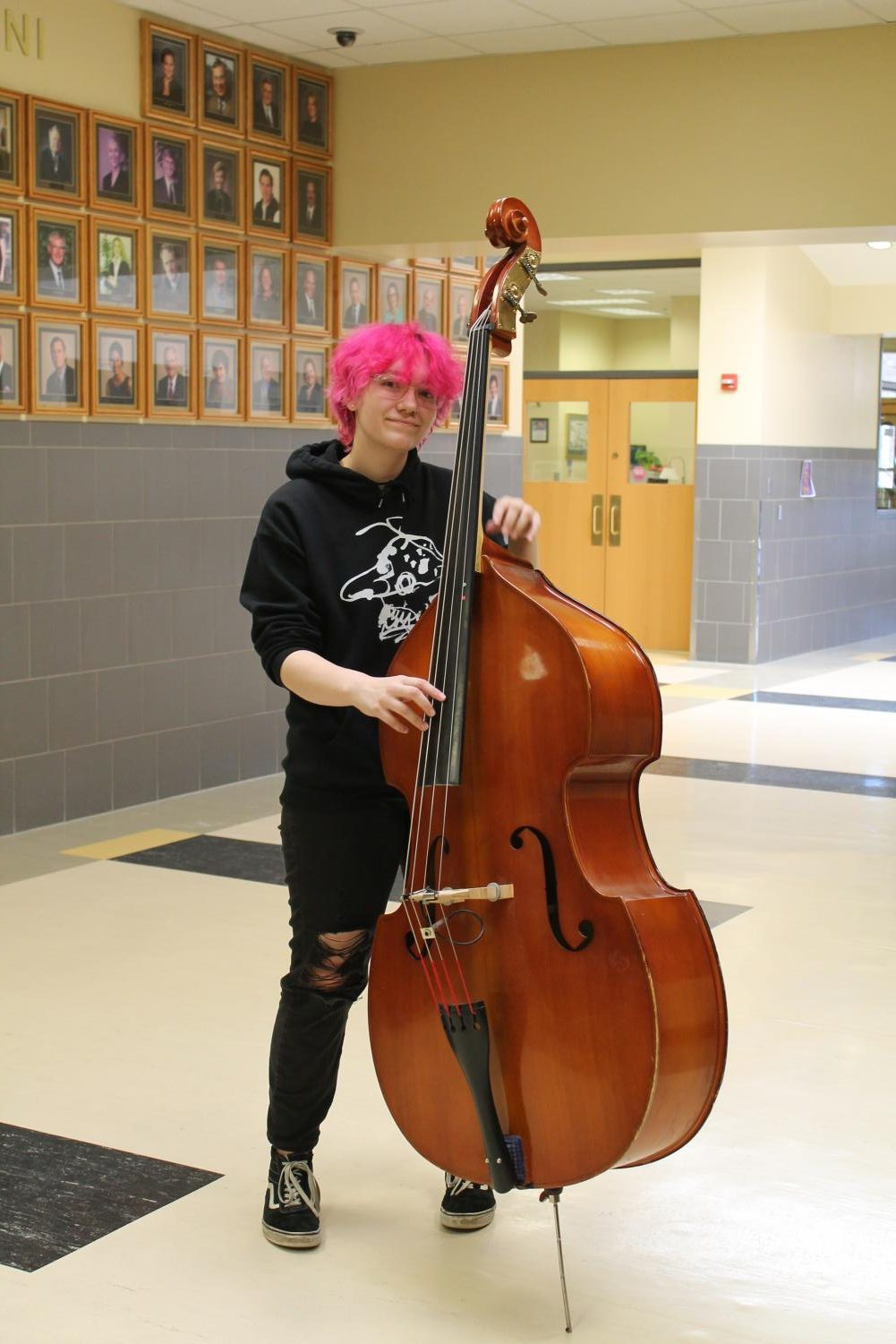 Tomasek poses with their bass of choice outside of the music hall.