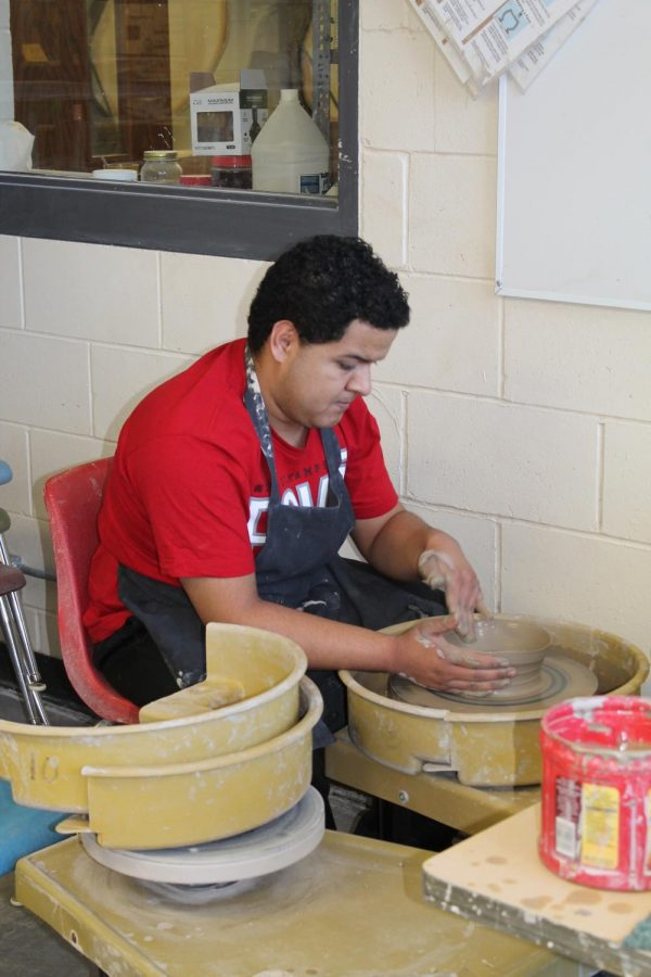 Julian+Silverio+%2812%29+gently+shapes+the+wet+clay+before+him+into+a+bowl.