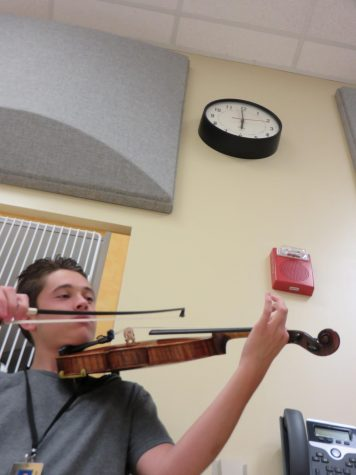 Senior Cyden Gonzales plays his violin down in the bounds of M-Hall