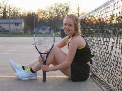 Senior Rachel Odabasi posing on a tennis court.