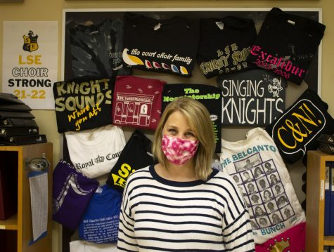 Southeast High School Choir Director Melissa Noonan poses in front of choir shirts from the past.